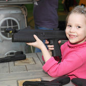 Girl playing with the big pistol — Stock Photo