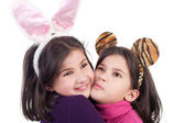 Sisters in the hare and tiger carnival ears embracing — Stock Photo