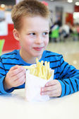 Boy with the french-fried potatoes — Stock Photo