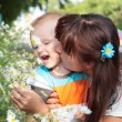 Child smelling flowers with his mother — Stock Photo