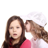 Girl whispering to her friend — Stock Photo