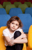 Little girl sitting in the cinema hall — Stock Photo