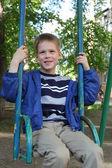 Liten pojke svänga i parken — Stockfoto