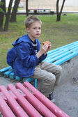 Boy eating hamburger in the park — Photo