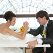 Bride and bridegroom arm wrestling — Stock Photo #51505489