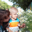 Child smelling the flowers with his mother — Stock Photo #51505637