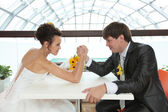 Bride and bridegroom arm wrestling — Stock Photo