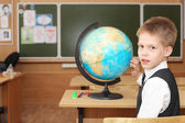 Little boy near a globe in a classroom — Stock Photo