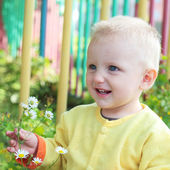 Child smelling the flowers — Stock Photo