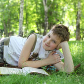 Boy reading a book on the grass — Stock Photo