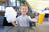 Little boy with juice and cotton candy — Stock Photo