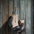 Brown old boxing gloves wooden wall — Stock Photo #15642091