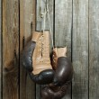 Brown old boxing gloves wooden wall — Foto de Stock