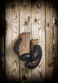 Brown old boxing gloves wooden wall — Stock Photo