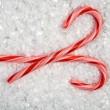 An image of two candy canes in the snow - Stock Photo