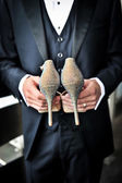 Groom holding bridal shoes — Stock Photo
