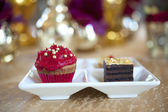 Fancy gourmet cupcake and slice of cake at a wedding — Stock Photo