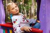 Fille sur une aire de jeux pour enfant avec divers manèges — Photo
