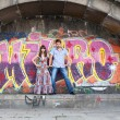 Couple jumping off the ledge with graffiti background — Stock Photo