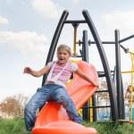 Girl riding rides on a child playground — Stock Photo
