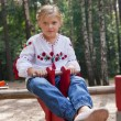 Girl on a child playground with various rides — Stock Photo #14035365