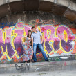 Couple jumping off the ledge with graffiti background - ストック写真