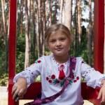 Child in Ukrainian style shirt on a swing — Stock Photo #14036092