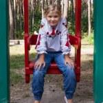 Child in Ukrainian style shirt on a swing — Stock Photo