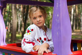Girl on a child playground with various rides — Stock Photo