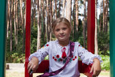 Niño en camisa estilo ucraniano en un columpio — Foto de Stock