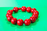 Wooden red beads on green background — Stock Photo