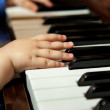 Baby hands playing piano — Stock Photo #25323737