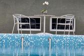 Twee stoelen en een tafel bij het zwembad — Stockfoto