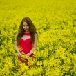 Beautyful teenager model in canola field — Stock Photo