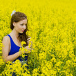 Beautyful teeny model in canola field — Stockfoto