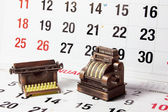 Cash Register and Typewriter on Calendar Pages — Stok fotoğraf