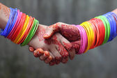 Shaking hands decorated with colorful bracelets — Stock Photo