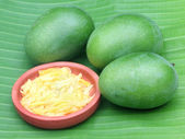 Fresh green mango over leafy background — Stock Photo