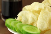 Potato chips with sliced cucumber and drinks — Stock Photo