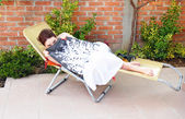 Young woman in outdoor chair — Stock Photo