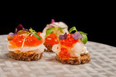 Salmon eggs, fish, and herbs canapes — Stock Photo