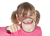Happy young girl showing tooth gap through magnifying glass — Stock Photo