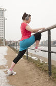 Young woman doing warm-up exercises for jogging — Stok fotoğraf