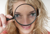 Woman looking through loupe and having two big eyes — Stock Photo