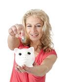 Uśmiechnięta kobieta oddanie pieniędzy monety w skarbonka — Zdjęcie stockowe