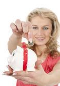 улыбается женщина положить деньги монеты в копилку — Стоковое фото