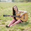 Woman playing guitar on a meadow — Stock Photo
