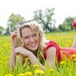 Happy woman lying down on dandelion field — Stock Photo
