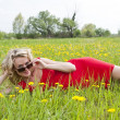 Woman enjoying dandelion field — Stock Photo