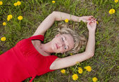 Woman sleeping in a field of grass with dandelions — Stock Photo